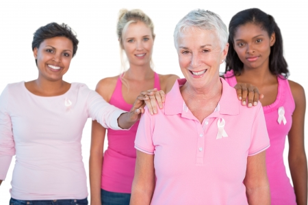 Supportive group of women wearing pink tops and breast cancer ribbons on white background photo