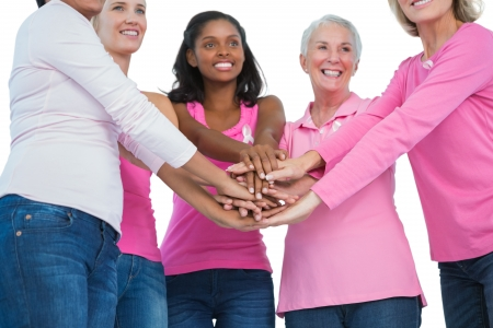 Happy women wearing breast cancer ribbons with hands together on white background photo