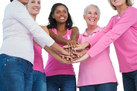 cancer de mama: Mujeres felices usando cintas de c�ncer de mama con las manos juntas sobre fondo blanco
