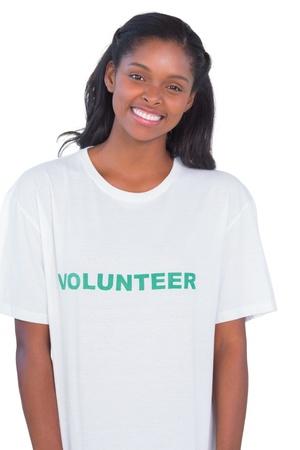 altruism: Sonriente mujer joven con camiseta de voluntario en el fondo blanco