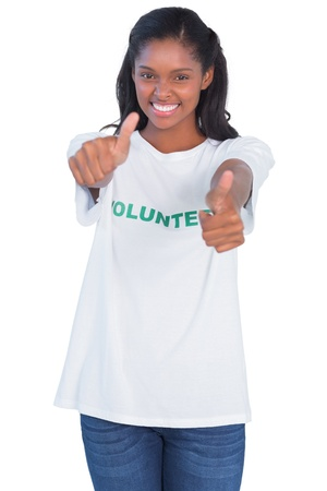 Young woman wearing volunteer tshirt and giving thumbs up on white background photo