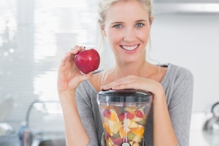 Blonde woman leaning on her juicer full of fruit and holding red apple at home in kitchen photo