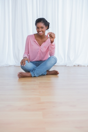 Cheerful young woman showing her new house keys and smiling at camera photo