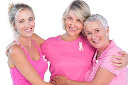 cancer: Women wearing pink tops and ribbons for breast cancer on white background