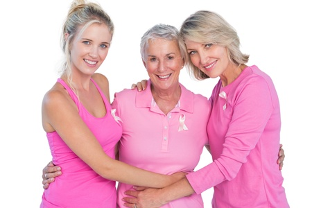 Happy women wearing pink tops and ribbons for breast cancer on white background