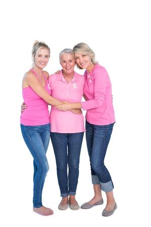 cancer de mama: Mujeres sonrientes vistieron camisas de color rosa y cintas para el c�ncer de mama en el fondo blanco Foto de archivo