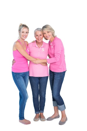 Smiling women wearing pink tops and ribbons for breast cancer on white background photo