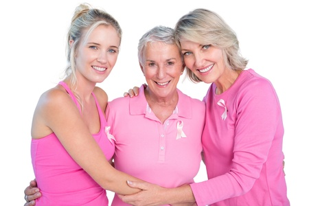 Embracing women wearing pink tops and ribbons for breast cancer on white background