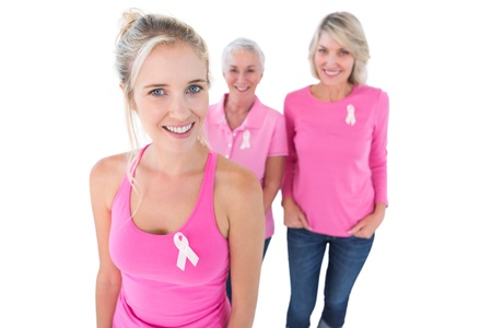Three generations of women wearing pink tops and breast cancer ribbons on white background