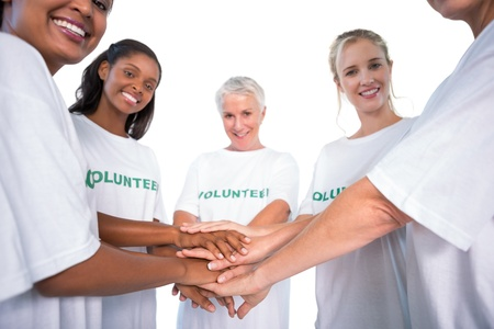 volunteerism: Group of female volunteers with hands together smiling at camera on white background Stock Photo