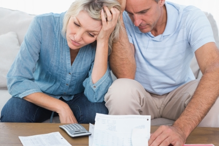 Worried couple going over bills at home in living room photo