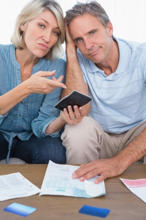 Anxious couple going over their debt looking at camera at home in living room Stock Photo - 20628999