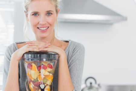 Blonde woman leaning on her juicer and smiling at camera at home in kitchen photo