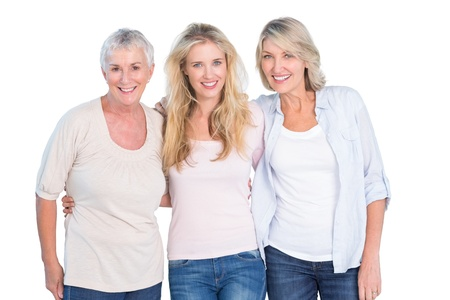 Three generations of women smiling at camera on white background photo