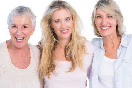 daughter: Three generations of  cheerful women smiling at camera on white background