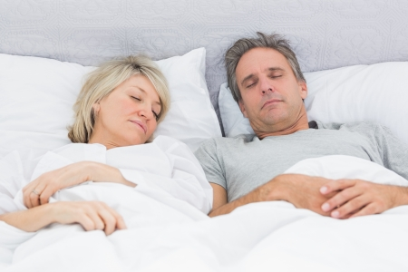 Couple sleeping peacefully in their bed at home in bedroom photo