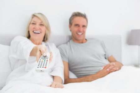 changing channel: Laughing couple watching tv in bed at home in bedroom Stock Photo