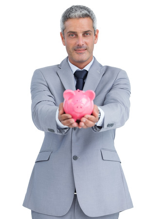 Confident businessman on white background holding piggy bank in both hands photo