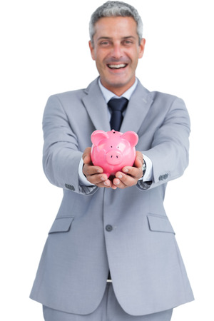 Wide smiling businessman on white background holding piggy bank  photo