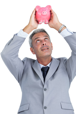 Curious businessman on white background holding piggy bank above his head photo
