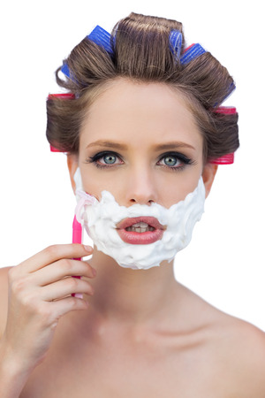 role reversal: Young model in hair curlers posing with shaving foam and razor on white background