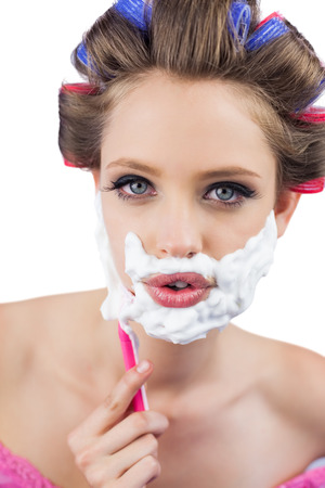 role reversal: Young model in hair curlers posing with razor in close up Stock Photo