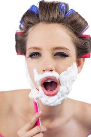 role reversal: Young model in hair curlers posing while shaving on white background