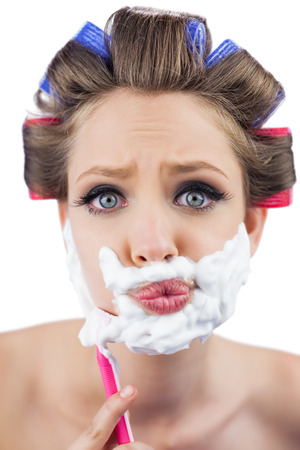 role reversal: Curious model in hair curlers posing with shaving foam and razor on white background