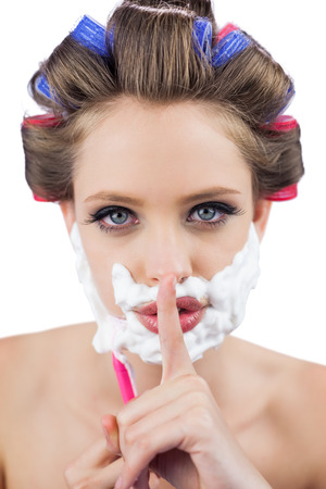 role reversal: Secretive woman in hair curlers posing with shaving foam and razor on white background Stock Photo