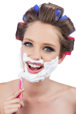 Smiling model in hair curlers posing while shaving on white background