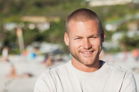 young man short hair: Handsome happy man posing on the beach Stock Photo