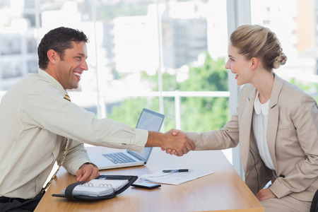 business interview: Blonde woman shaking hands while having an interview in office