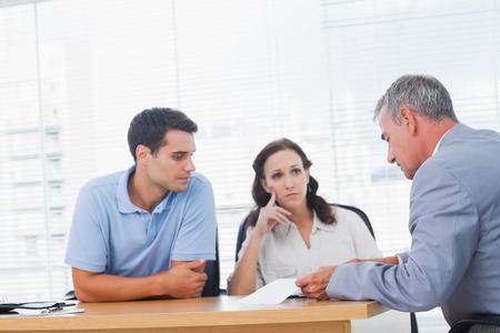Serious couple negociating with real estate agent in bright office Stock Photo