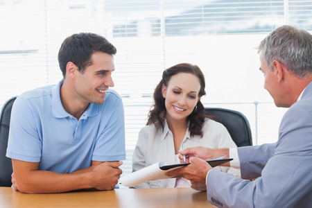 real estate agent: Smiling couple signing contract with real estate agent in bright office