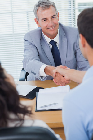 real estate agent: Smiling real estate agent shaking hands with his new buyer in bright office Stock Photo