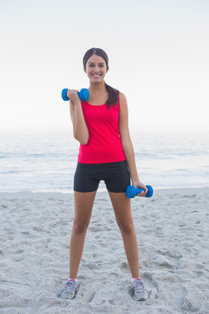 woman lifting weights: Sporty woman exercising with dumbbells on the beach