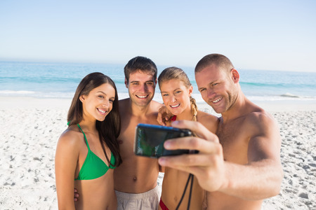 Smiling friends taking pictures of themselves on the beach photo