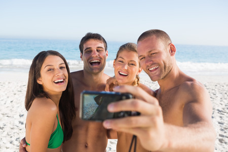 Cheerful friends taking pictures of themselves on the beach photo
