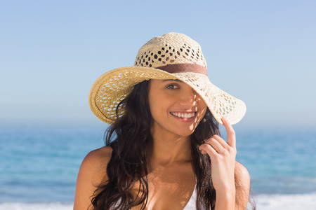 dark haired woman: Attractive dark haired woman with straw hat posing on the beach Stock Photo