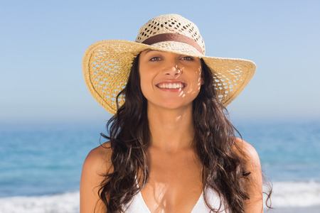 dark haired woman: Smiling attractive dark haired woman wearing straw hat posing on the beach