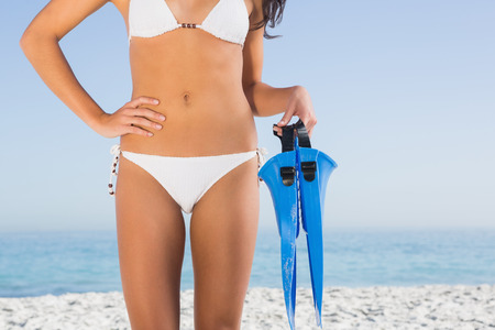 perfect female body: Perfect female body in white bikini holding fins on the beach Stock Photo