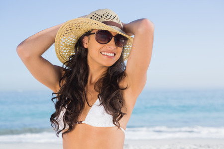 Cheerful attractive brunette with straw hat and sunglasses on the beach photo