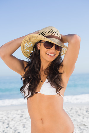 Happy attractive brunette with straw hat and sunglasses on the beach photo