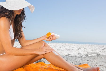 sun protection: Close up of sexy young woman on the beach applying sun cream