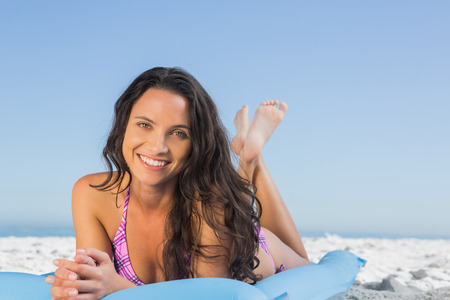 Happy attractive brunette lying on her lilo on the beach photo