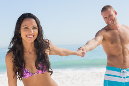 sexy couple on beach: Smiling couple holding hands on the beach