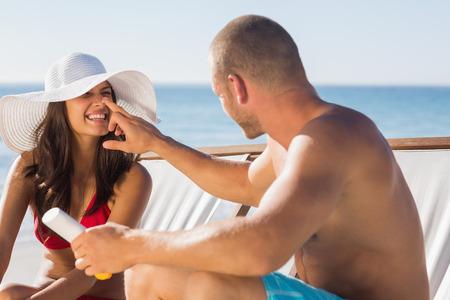 Handsome man applying sun cream on his girlfriends nose on the beach photo