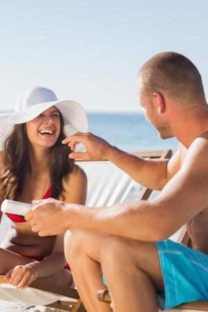 Attractive man applying sun cream on his girlfriends nose on the beach photo