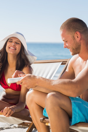 Attractive man applying sun cream on his girlfriend on the beach photo