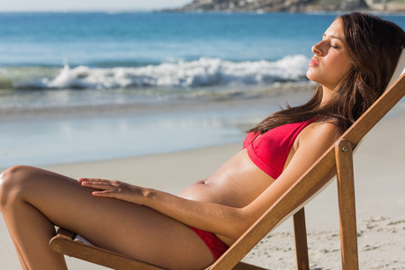 Pretty woman relaxing on her deck chair on the beach photo